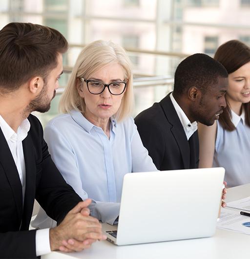 Team arbeitet zusammen an Laptops, um die Anforderungen herauszuarbeiten