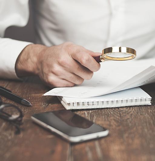 Mann liest Vertragsunterlagen auf Papier mit Lupe